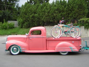 Older pink truck with bikes on the back